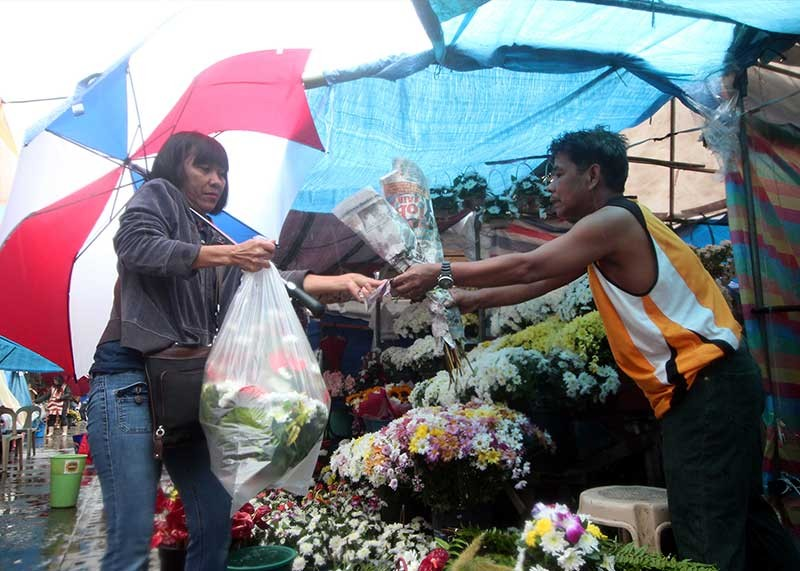 A lady purchases flowers at the Ganza parking area in Burnham Park amid the heavy downpour. Vendors say that due to the weather, fewer customers are able to ...