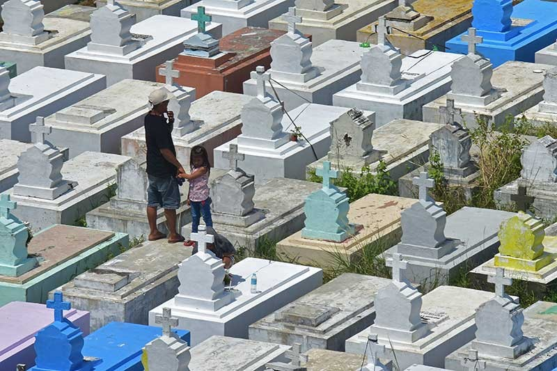 DAVAO. A young girl, together with her father, visits the Roman Catholic Cemetery in Davao City yesterday in observance of the All Saints' Day. Hundreds are expected to gather at the cemetery to visit their departed loved ones during the Undas season. (Macky Lim)