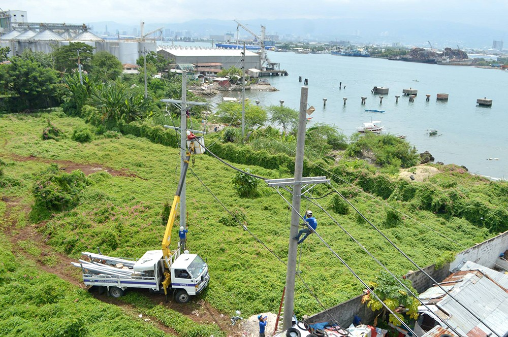 POWER TO THE PEOPLE. Personnel of the Mactan Electric Company install power lines for households in Barangay Pajo, Lapu-Lapu City. While this area is connected to the main grid, many islands in the country are not. (SunStar file)