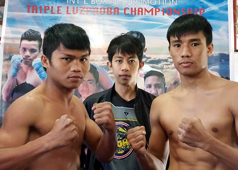 BAGUIO. Ivor Lastrilla of Highland Boxing Gym and Dan Manosa (Metro Manila) face off for the LuzProBA lightweight title during their weigh – in Monday morning. With them is boxing promoter Darwin Miller Dep-ay. (Contributed photo)