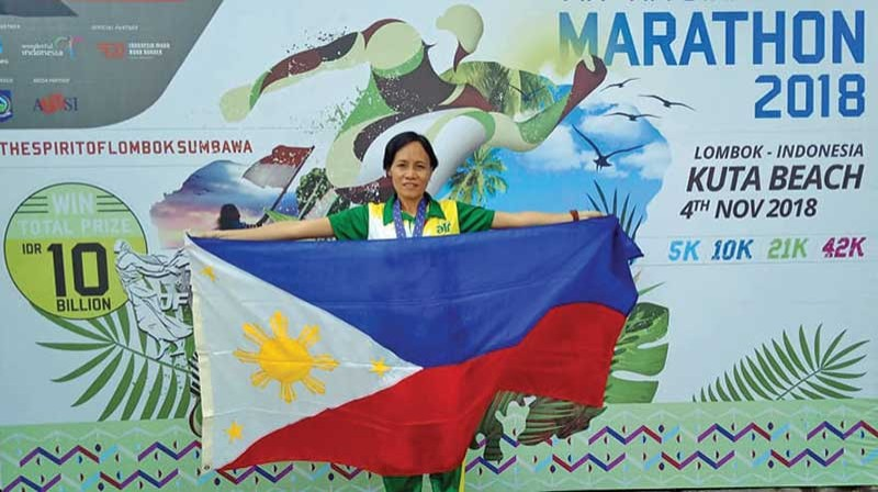 PROUD PINAY. Corporal Jho-An Banayag Villarma poses with the Philippine flag after salvaging a bronze medal in the women's 21K event of the TNI International Marathon 2018 Inter-Armed Forces/Police in Lombok, Indonesia. (Contributed photo)