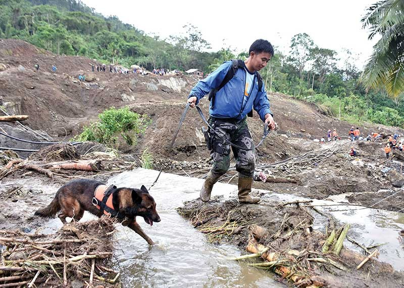 MOUNTAIN PROVINCE. A K9 unit and his trainer scour Ground Zero in Natonin, Mountain Province where more than 20 individuals are believed to have been buried alive. The landslide led to the collapse of DPWH Mountain Province Second District Engineering Office and some nearby houses in Sitio Ha'rang, Barangay Banawel. (Photo by Redjie Melvic Cawis)