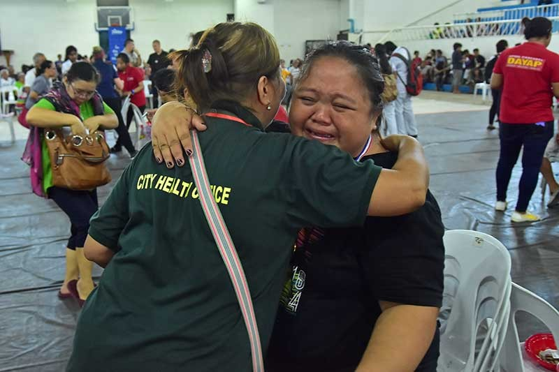 HEARING AGAIN. Dodith Alferaro, 34, hugs the staff of the Davao City Health Office with tears of joy for being able to hear again after a very long time after she received the hearing aid from Starkey Hearing Foundation on Tuesday, November 6, during their medical mission in Davao City held at the Davao City Recreation Center. (Macky Lim)