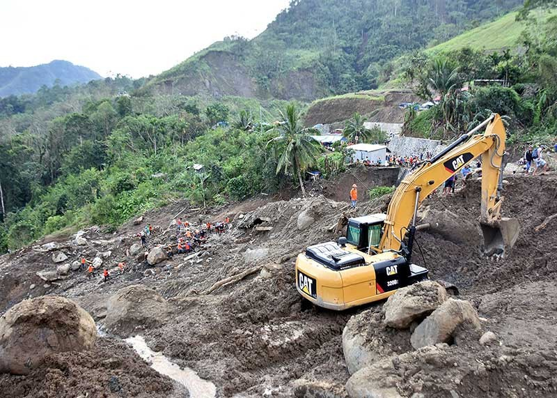 BAGUIO. Volunteers and a heavy equipment work hand in hand to retrieve individuals believed to have been buried in a landslide that hit the DPWH Mountain Province Second District Engineering Office and some nearby houses in Sitio Ha'rang, Barangay Banawel, Natonin, Mountain Province during the height of typhoon Rosita last week. (Redjie Melvic Cawis)