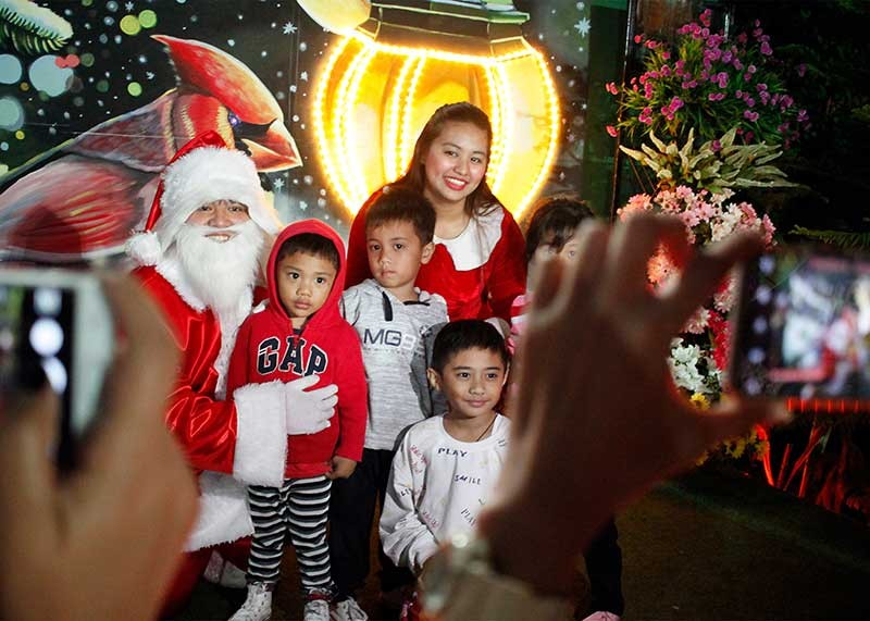BAGUIO. Families enjoy taking photographs at the Baguio Country Club's Christmas village. Despite the rumored closure of Baguio City, tourist continue to flock the highland resort especially with the declining temperature which is expected to change in the coming days. (Jean Nicole Cortes)