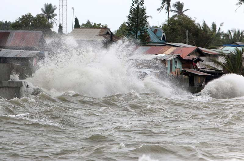 BIG WAVES. A low pressure area sends waves crashing against houses in Barangay Poblacion, Talisay City, damaging several houses in coastal villages. (SunStar photo/Alex Badayos)