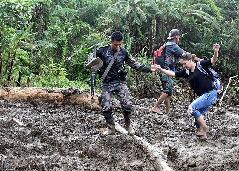 MOUNTAIN PROVINCE. Communications Assistant Secretary Marie Rafael Banaag, a former mayor of Natonin town, passes through a landslide-hit road on her way to Sitio Ha'rang, Barangay Banawel in Natonin, where more than 20 people were buried when a landslide struck a Department of Public Works and Highways (DPWH) building as Typhoon Rosita pummeled the area. (Photo by Redjie Melvic Cawis)