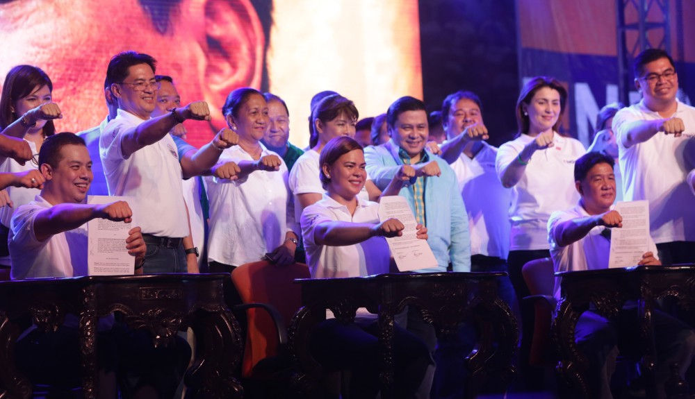 TACLOBAN CITY. Leyte 1st District Congressional Candidate and Lakas-CMD Party President Martin Romualdez (left seated) together with Hugpong ng Pagbabago Chairperson and Davao City Mayor Sara Duterte (center seated) and Tingog Party List Chairman Mark Gimenez (right seated) shows the copy of their signed Party Alliance and flashes a President Rodrigo Duterte's trademark close fist as well as other candidates from right standing Jude Acidre of Tingog, Leyte Rep. Yedda Marie Romualdez of Tingog, Alexis Yu of Tingog, senatorial candidates Jinggoy Estrada, Governor Imee Marcos, Harry Roque, Butuan City Vice Mayor Joboy Aquino, and Bacoor City Mayor Lani Mercado representing her husband Bong Revilla, during the Signing of Alliance Ceremony at Tacloban City Astrodome on November 7. (Photo by Ver Noveno)
