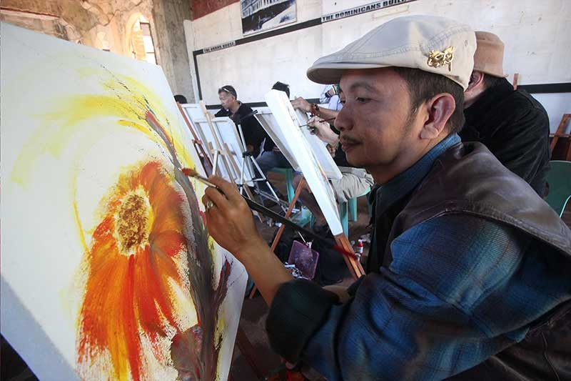 """ON THE SPOT. Local artists bring magic to a blank canvas as they paint at the Diplomat Hotel during the celebration of the first creative festival in Baguio, """"ENTACool."""" (Photo by Jean Nicole Cortes)"""