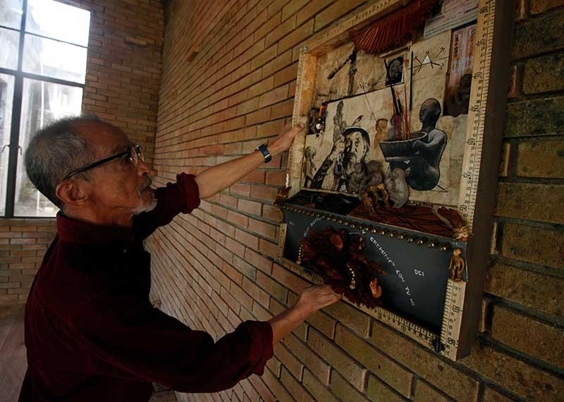 BAGUIO. Artist Willy Magtibay checks on artwork displayed at the Diplomat Hotel as part of the Baguio Creative Festival, 'EntaCool.' Magtibay lashed out at the festival saying issues on cultural appropriation and exploitation must be addressed. (Jean Nicole Cortes)