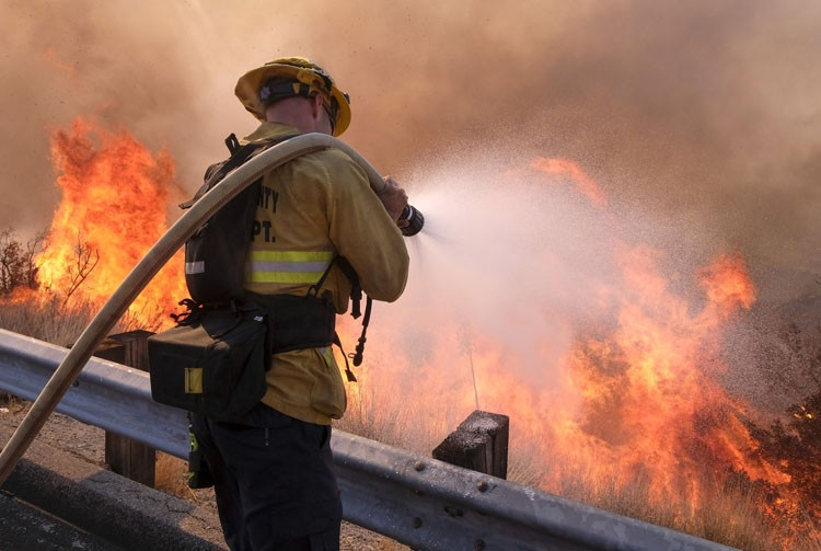 USA. A firefighter battles a fire along the Ronald Reagan (118) Freeway in Simi Valley, Calif., Monday, Nov. 12, 2018. (AP Photo/Ringo H.W. Chiu)