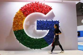 SHANGHAI. In this Monday, Nov. 5, 2018, photo, a woman carries a fire extinguisher past the logo for Google at the China International Import Expo in Shanghai. Internet traffic hijacking disrupted several Google services Monday, Nov. 12, 2018, including search and cloud-hosting services. (AP)