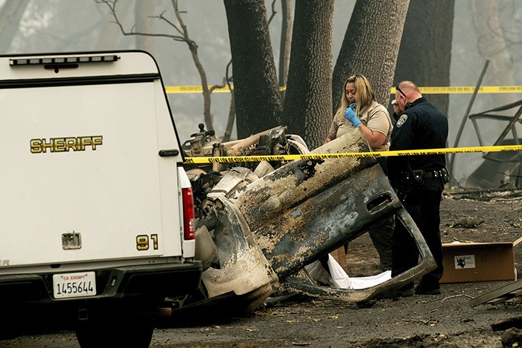CALIFORNIA. A sheriff's deputy recovers the remains of a Camp Fire victim from an overturned car in Paradise, California, on Thursday, Nov. 15, 2018. (AP Photo/Noah Berger)
