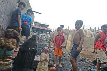 SALVAGING. Children join the men in trying to retrieve some images of saints from the ashes after the fire in Barangay Lorega, Cebu City. (SunStar photo/Amper Campaña)