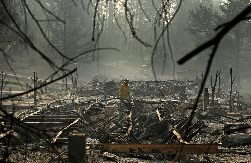CALIFORNIA. A firefighter searches for human remains in a trailer park destroyed in the Camp Fire, Friday, Nov. 16, 2018, in Paradise, Calif. (AP)