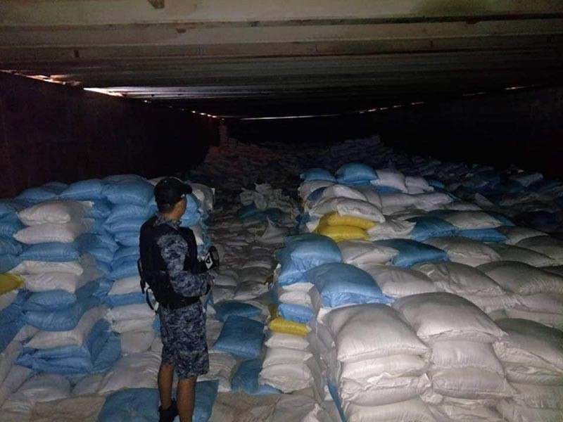 ZAMBOANGA. A personnel of the Zamboanga Coast Guard Station guards the thousands of sacks of rice intercepted in the Sulu Sea on Saturday, November 17. (Contributed photo)