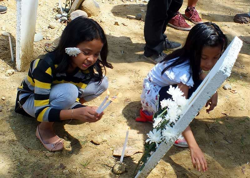 MAGUINDANAO. In remembrance, Eleanor Dalmacio's daughters offer flowers at her marker in Ampatuan town during the commemoration of the Maguindanao massacre. (Photo by Ma. Elena Catajan)