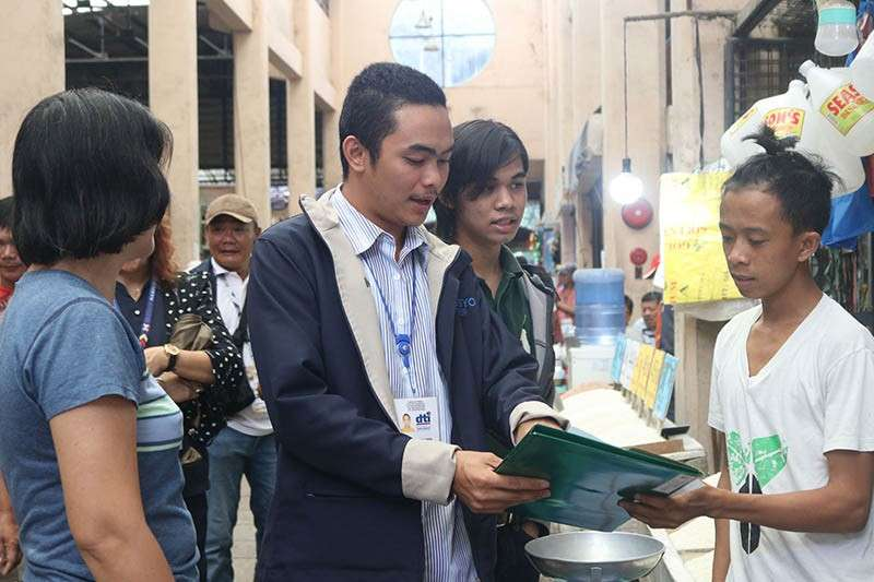 Kher Jake Martin Trayco (center) of the Department of Trade and Industry along with other members of the Local Price Coordinating Council checks the SRP compliance of rice retail outlets at the public market of Bago City. (Contributed Photo)