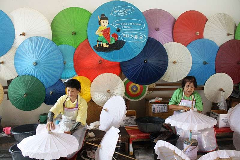 THAILAND. Workers glue the paper on the struts. (Claire Marie Algarme)