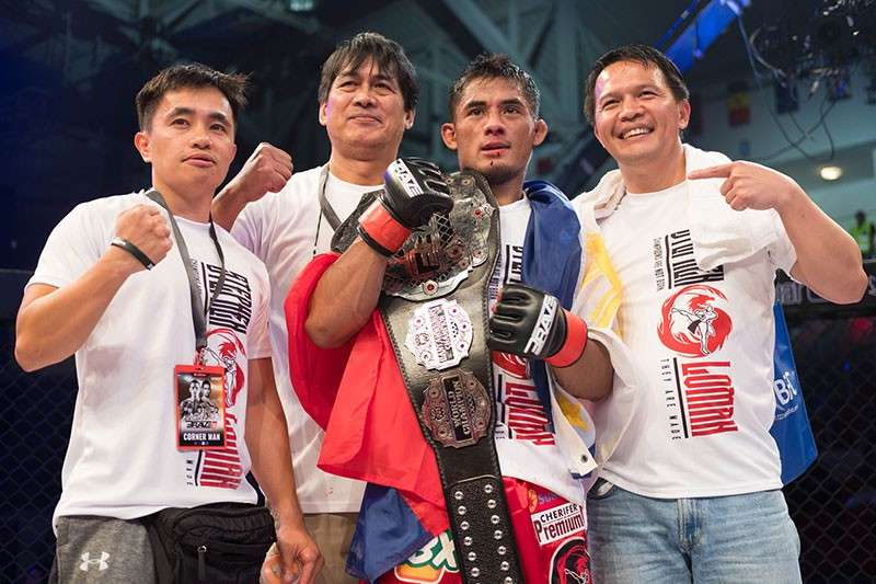 BAGUIO. Stephen Loman is joined by Team Lakay coach Mark Sangiao and supporters after retaining the bantamweight world title in Brave Combat Federation earlier this month. (Photo courtesy of Brave CF)