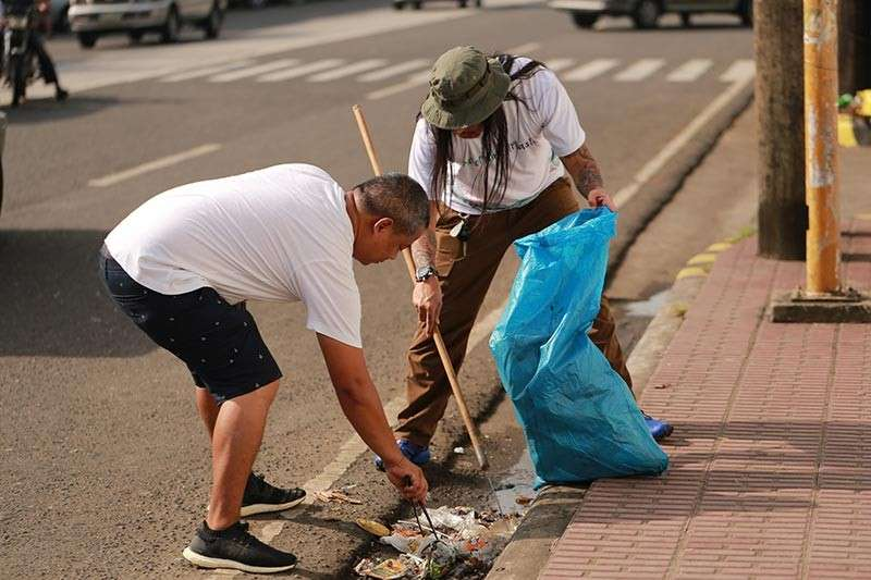 CLEANUP. Volunteers pick up plastic trash on the street during the recent MassKara SweepWalk or picking-up trash along the way while walking for exercise. The event was organized by SM City Bacolod and the Philippine Reef and Rainforest Conservation Foundation. (Contributed photo)
