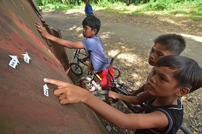 DAVAO. Young bikers take a closer look at the bullet holes at the gate of a property in Victorio Road, Barangay Talomo, Davao City left by the firefight between the police and the rebels early morning Monday, November 26. (Macky Lim)