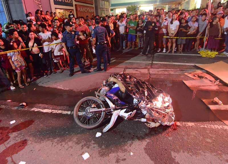 SHOT DEAD. The bodies of the two ex-cops are covered with a foil blanket. (SUNSTAR photo/Alan Tangcawan)