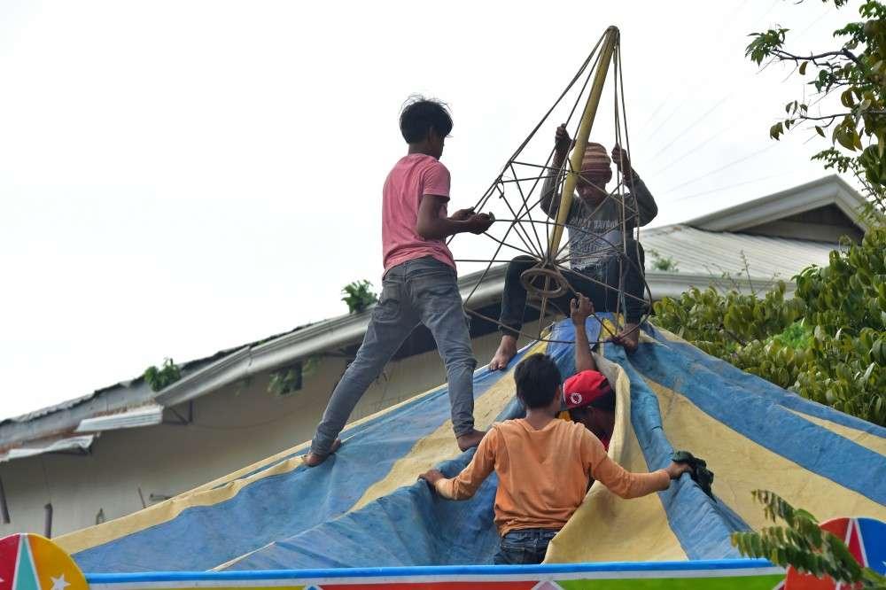 """DAVAO. Mga trabahante sa perya gipaspasan og human Huwebes, Nobyembre 29, ang """"rides"""" nga modalit og libreng sakay sa mga moduaw sa Rizal Park, Davao City alang sa pagsaulog sa Pasko Fiesta. (Macky Lim)"""