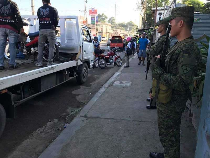 CHECKPOINT. Soldiers stand guard as members of the Inter-Agency Council for Traffic check the motorists' documents in Barangay Linao, Talisay City. (Contributed photo)