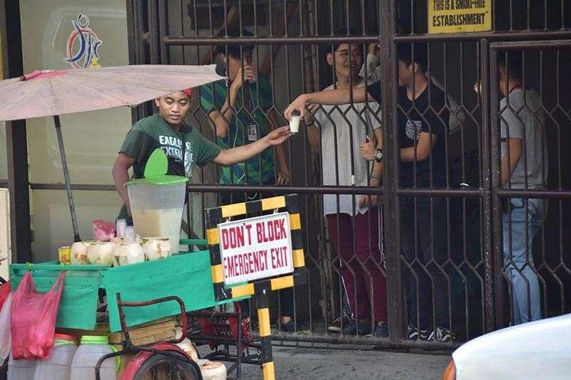 DAVAO. Mga estudyante sa usa ka unibersidad sa may dalang Bolton sa siyudad sa Davao namalit og buko juice sa vendor nga nahimutang sa dalang Palma Gil aron mawagtang ang kauhaw ug aron di na sab mogawas sa maong tunghaan. (Macky Lim)