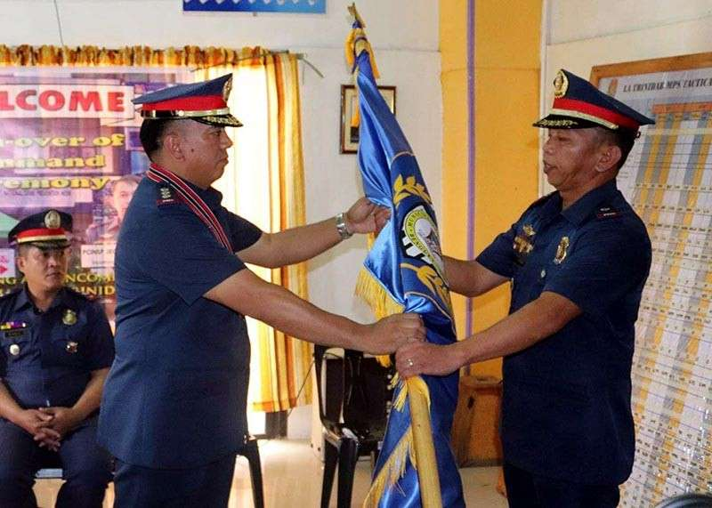 BENGUET. Benguet Provincial Police Office Director Lyndon Mencio hands over to Chief Inspector Jeoffer Banglayan the La Trinidad Municipal Police Station flag after swearing in as the town's top cop. (Contributed photo)