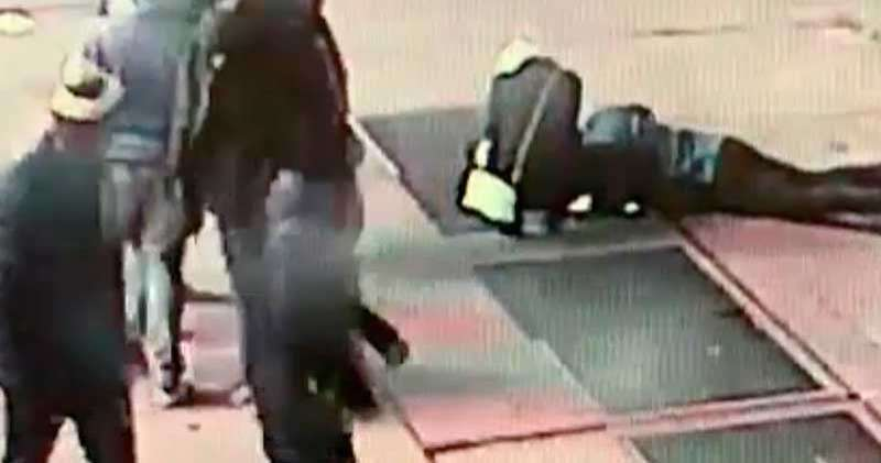 In this Nov. 30, 2018 image taken from surveillance video provided by the New York City Police Department, a man tries to see the engagement ring that he dropped down a utility grate on New York's Times Square. The New York City Police Department says the man was proposing to his girlfriend just before midnight Friday when he dropped the ring and it fell about eight feet down the utility grate. (AP)