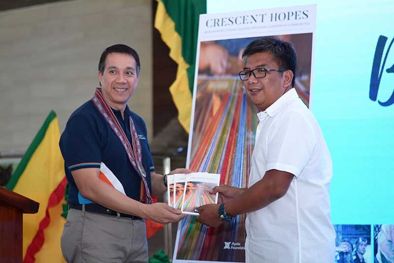"""CAGAYAN DE ORO. Ayala Foundation President Ruel Maranan presents copies of the book """"Crescent Hopes"""" to ARMM Regional Governor Mujiv Hataman. """"Crescent Hopes"""" gathers inspiring stories of personal and community transformations, as experienced by the BYLP–LeadCom fellows. (Contributed Photo)"""