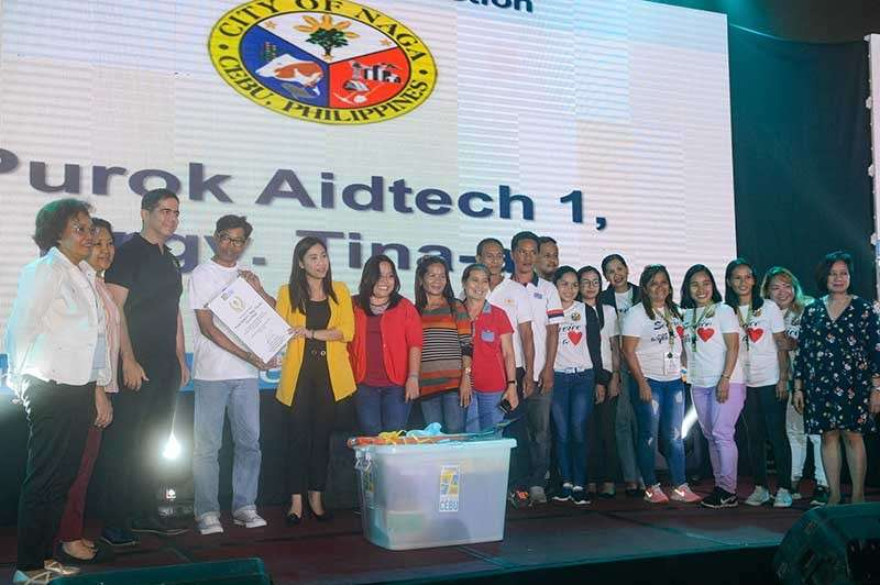 RECOGNITION. Members of the Purok Aidtech 1 of Barangay Tina-an, City of Naga, Cebu receive an award from the Metro Cebu Development Coordinating Board during the Mega Cebu Purok Awards. With them is Naga City Mayor Kristine Chiong (fifth from left). (Contributed photo)