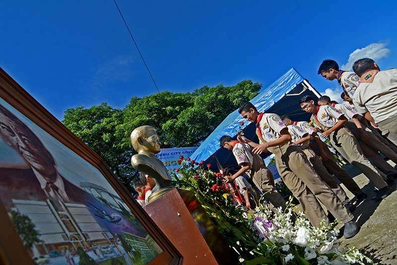 BIRTHDAY HONOR. Boy Scouts lay flowers at the foot of the brass image of Sergio Osmeña Jr. at the Plaza Independencia to commemorate his 102nd birthday. (SunStar photo/Amper Campaña)