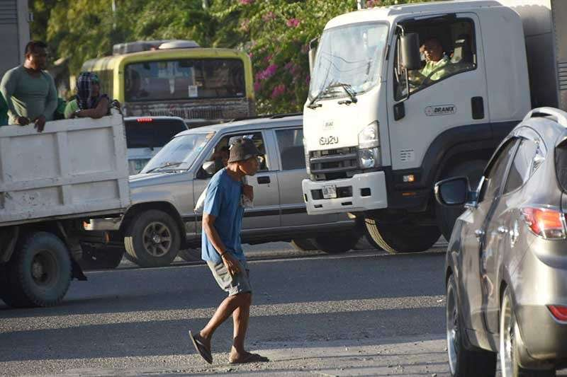 TRAFFIC. A man braves the street of Mandaue City amid slow-moving traffic. (SunStar photo/Allan Cuizon)