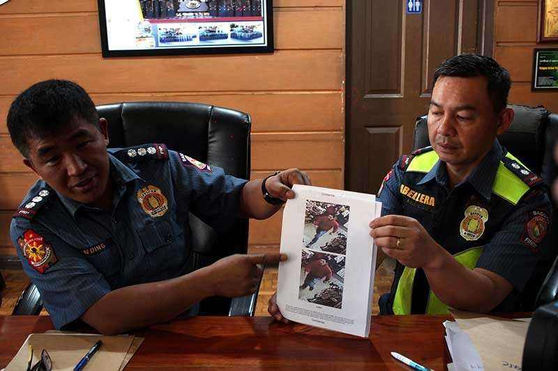 BAGUIO. Chief Superintendent Eliseo Tanding and Superintendent Yamson Abellera shows photos grabbed from a camera footage showing the men who gunned down Imam Bedejim Abdullah, a Muslim leader and preacher at the Kayang Business Center at the Public Market, on December 6. (Photo by Jean Nicole Cortes)