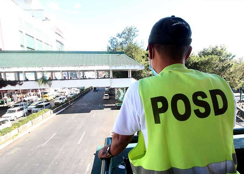 BAGUIO. A Public Order and Safety Division officer monitors the overpass along Harrison road. (Photo by Jean Nicole Cortes)