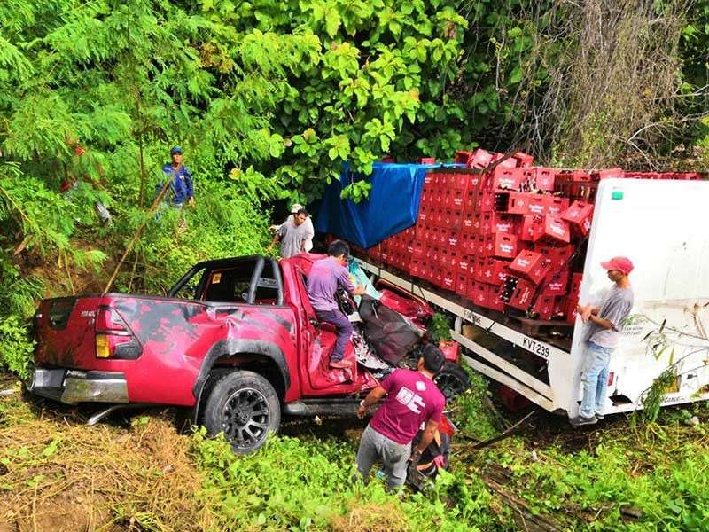 First responders pull out the two people inside the pick-up vehicle rammed by a 10-wheeler truck towards the ravine in Laguindingan, Misamis Oriental, over the weekend. The crash left a woman killed and another seriously wounded. (Contributed photo)