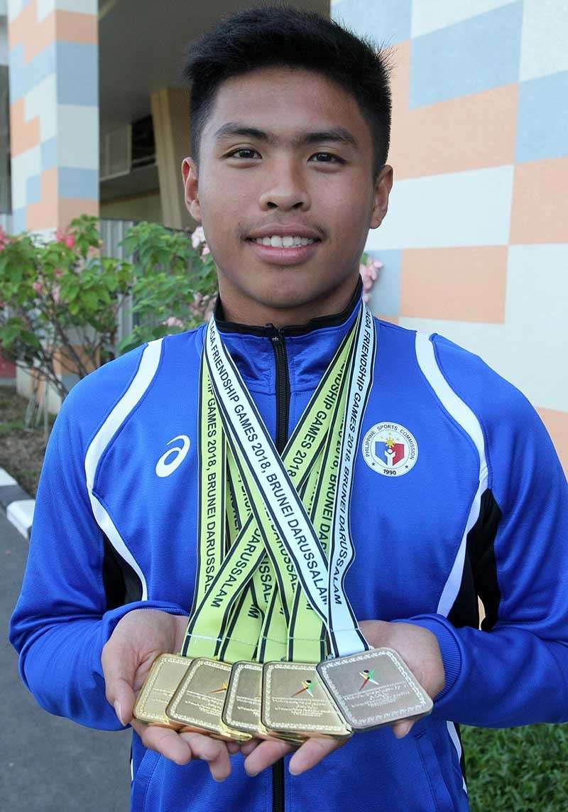 MOST BEMEDALED. Davao swimmer Fritz Jun Rodriguez shows the four gold medals and one silver he collected at the close of the 10th BIMPNT-Eaga Friendship Games swimming competition Saturday afternoon, making him the most bemedaled athlete at the Hassanal Bolkiah National Sports Complex in Brunei. (Contributed photo)