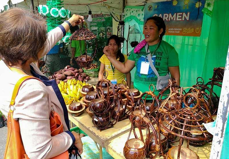 SUPPORTING LOCAL CRAFTS. A customer at the Pasko sa Kapitolyo 2018 checks out the wooden creations being sold from Carmen. Small business owners hope Christmas shoppers will consider local goods when buying presents. (SunStar photo/Arni Aclao)