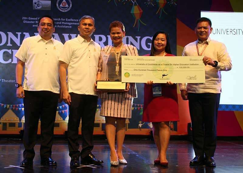 BAGUIO. The University of the Cordilleras (UC) was among the Top 3 finalists for Best Higher Education Institutions in Disaster Risk Reduction and Management (DRRM) and Humanitarian Assistance in the 2018 National Gawad Kalasag. UC VP for administration Dr. Leonarda Aguinalde (center), UC chief librarian Beverly Chapichap (2nd from R), and OCD-CAR regional director Albert Agoncillo Mogol (R) receives the plaque and P100,000 cash prize from Deputy Civil Defense Administrator Asec. Kristoffer James Purisima (L) and NDRRMC Executive Director and Civil Defense Administrator USec. Ricardo B. Jalad (2nd from L). (Photo by Rene Verdote)