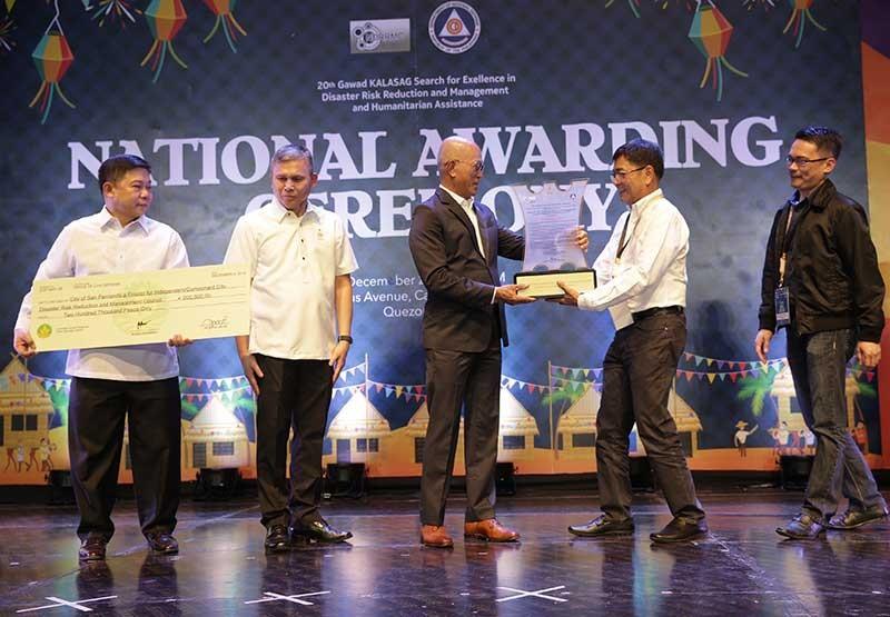 PAMPANGA. City of San Fernando Mayor Edwin Santiago and CDRRMO head Raymond Del Rosario receive the Gawad Kalasag trophy from Defense Secretary Delfin Lorenzana. (Contributed Photo)