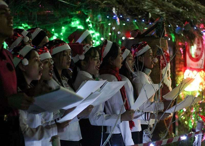BAGUIO. A choir serenades visitors with Christmas carols at the mini Christmas village in La Trinidad. (Jean Nicole Cortes)