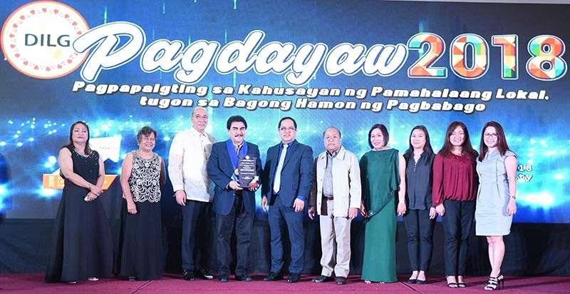 """ILOILO. Local officials led by Mayor Evelio Leonardia receive the award for Bacolod as first runner-up in the """"Excellence in Administrative Governance"""" category of the Department of Interior and Local Government 2018 Regional Seach for Excellence in Local Governance (Excell) held in Iloilo City on Wednesday, December 12. (Contributed photo)"""
