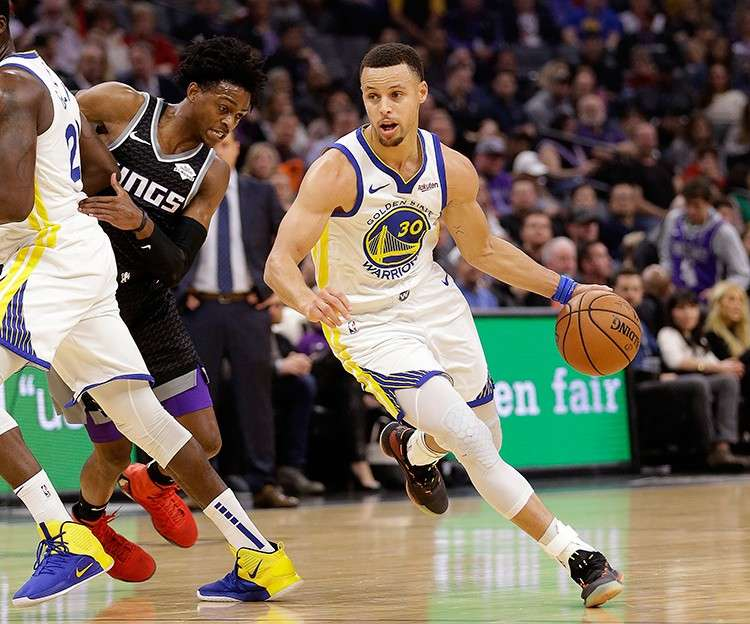 Milusot. Si Stephen Curry, tuo, sa defending champion Golden State Warriors nga nangitag kalutsan taliwala sa hugot nga depensa ni Sacramento Kings guard De'Aaron Fox, tungo, kinsa naigo usab sa screen ni Draymond Green sa Warriors. (AP)