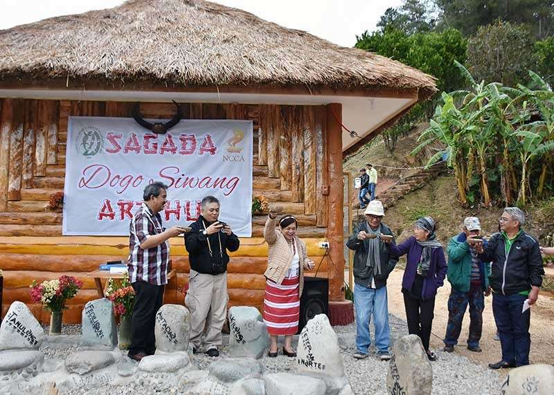 SAGADA. The National Commission on Culture and the Arts with the Cordillera News Agency (CNA) and the Daoas family formally opened the Sagada Dugo Siwang Art Hub aimed to champion indigenous knowledge both for locals and visitors for the preservation and continuing exchange of knowledge, arts, culture and heritage. A ceremonial toast was held during the opening ceremonies with (from left) property owner lawyer David Daoas, artist Philip Del Carmen, CNA Executive Director Sonia Daoas, CNA vice president Domci Cimatu, CNA member Merce Dulawan and Sagada Mayor James Pooten. (Photo by Redjie Melvic Cawis)