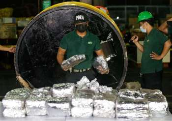 MANILA. A member of the Philippine Drug Enforcement Agency (PDEA) collects packs of methamphetamine hydrochloride also known as