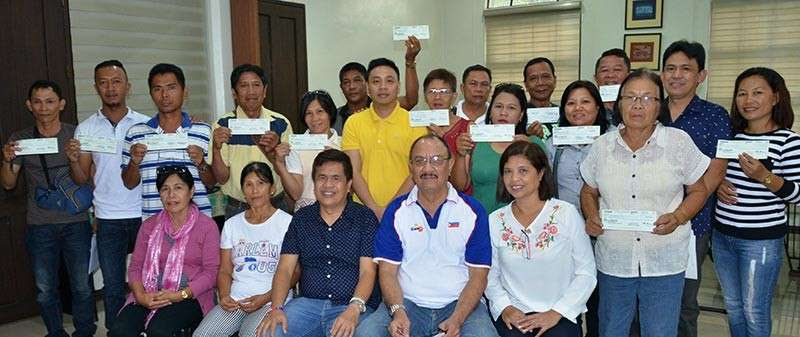 turnover of cheNEGROS. Executive Assistant to the Governor Angel Verdeflor (seated, 2nd from right) and Fifth District Board Member Renato Malabor Jr. during the turnover of checks worth P4.3 million to the barangay officials of the Municipality of Isabela, Tuesday, December 18. (Contributed photo)