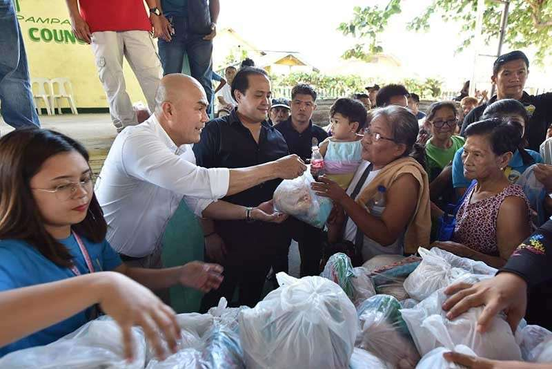 """PAMPANGA. Vice Governor Dennis """"Delta"""" Pineda, Mabalacat City Mayor Crisostomo Garbo and the provincial board members distribute Christmas gifts to 11,012 Mabalaqueños. Assisting them are BM Cherry Manalo, PSWDO headed by Elizabeth Baybayan and PDRRMO head Angie Blanco. (Photo by Jun Jaso)"""